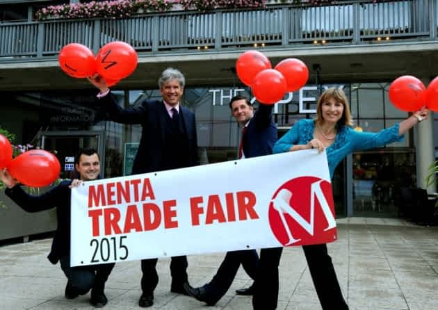 Staff members of Menta holding balloons at the trade fair we attended as a website design company